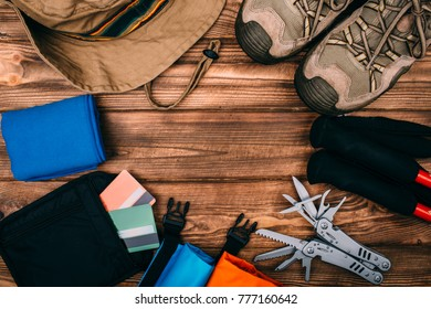 Top view of equipment for hiking and travel on wooden table withempty space in the middle. Items include trekking pole, shoes, multi tool, hat, towel, hermetic bag, payment cards