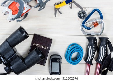 Top view of equipment for mountaineering and hiking on white wood table with empty space in the middle. Items include rope, passport, carbines, knife, compass, binoculars, trekking pole and gps.