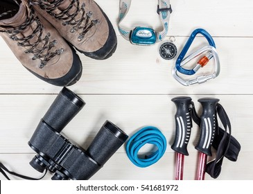 Top view of equipment for mountaineering and hiking on white table with empty space in the middle. Items include rope, passport, carbines, shoes, compass, binoculars, trekking sticks and flashlight.