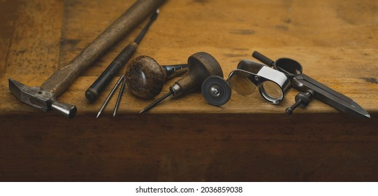 Top view of equipments for jewelry work on antique wooden desktop. Jeweller, engraver at work on jewelry made of diamonds and gold