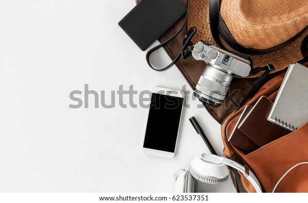 Top view of essential modern. travel accessories on white wooden table background. over light