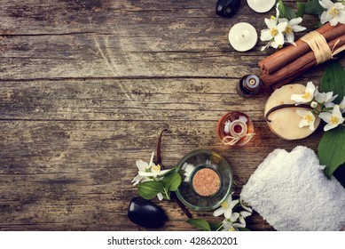 Top view of essential oils with jasmine, cinnamon and vanilla on rustic wooden table, retro style. Spa and wellness aromatherapy treatment. Asian massage and skin care background design.