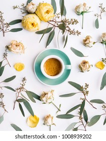 Top view of a eucalyptus branches and dry roses chaotically lying on the white background making a floral pattern with a cup of fresh espresso coffee with beautiful crema background