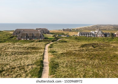 Top view in the evening: Path through the nature reserve and the dunes near village Kampen on the North Sea island of Sylt, with houses and hotels with thatched roof and the sea in the background
