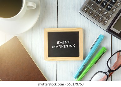 top view of EVENT MARKETING written on the chalkboard,business concept.chalkboard,notebook,calculator,pen,glasses,coffee on the wooden desk.