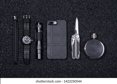 Top view of everyday carry (EDC) military items for men in black color - multi tool, lighter, mobile phone, tactical watch, paracord survival bracelet,flashlight and flask. Flat lay.