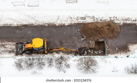 top view of excavator digging road to change sewer pipes in winter in Moscow city