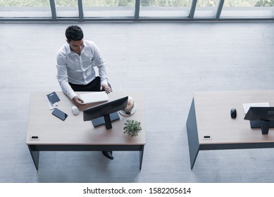 Top view of executive, manager, or engineer drinking coconut juice working on computer sitting in creative office prepare travel document for summer trip