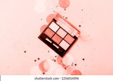 Top view of Eye shadows palette on Living Coral confetti background. Concept of creative color of year 2019 16-1546. Bright and festive. Holiday fashion cosmetic set. Copyspace for text