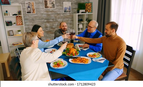 Top view of family clinking glasses with red wine while making a toast during dinner with delicious food.