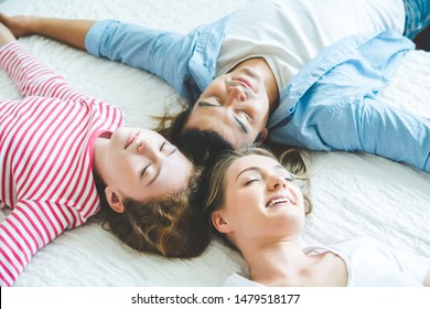 Top view of family cute looking , happiness looking at the camera and smiling while lying on the bed at home
