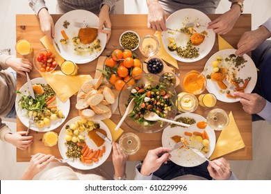 Top view of family eating healthy meal beside table