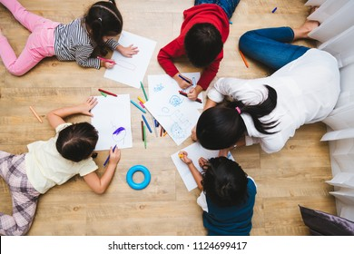 Top view Family happy children group kid boy and girl kindergarten paint drawing on peper with teacher education together at interior playroom