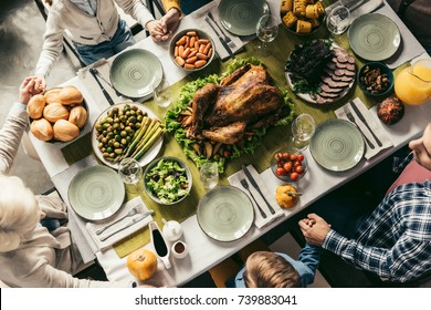 top view of family having holiday dinner with delicious turkey on thanksgiving