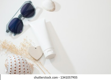 top view with fashio sunglasses summer concept of spa sea beach beauty cosmetic body lotion cream aroma perfume sunscreen spf mockup package product with shell and flower on table
