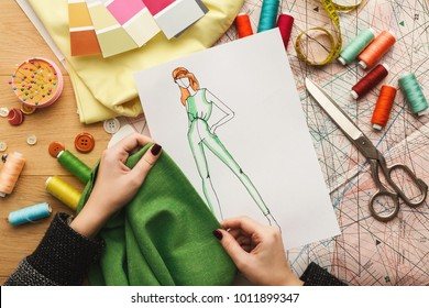 Top view of fashion designer working with material sample and hand-drawn sketch at messy table background, top view. Dressmaking, creativity and sewing workshop concept