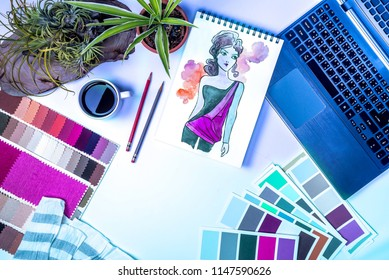 Top view of fashion designer's desk with drawing, laptop computer & fabric swatch at creative office