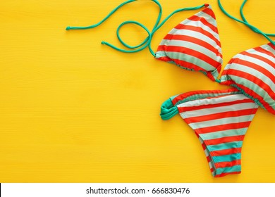 Top view of fashion female swimsuit bikini on yellow wooden background. Summer beach vacation concept