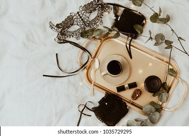 Top view fashion gold and black  accessories. Mask, coffee, lipstick and lace lingerie. Set of woman essential accessory and underwear on flat lay.