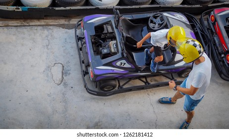 Top view of father and son preparing for gokart in a two seater car.