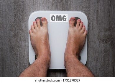 Top view of the feet of a barefoot man standing on smart scales, on whose balance it is written oh my God. White smart weights with empty balance standing on a gray wooden floor.