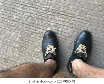 Top view of feet in black leather shoes on cement floor.casual style on vacation.man foot in shoes.