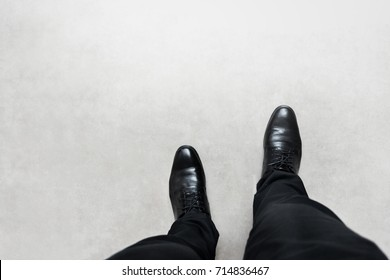 Top view feet of businessman in black shoes walking on grey road. walking go to dream concept.