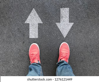 top view of feet and different direction arrows on asphalt road