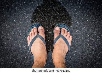 ce19b8bd663b47 Top view feet in sandals selfie shot of asian men legs with wet street