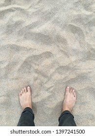 Top view of feet standing in sand at a beach
