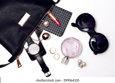 Top view of female accessories for woman. Fancy sunglasses, leather bag , watch , lipstick , perfume , rings , mobile phone