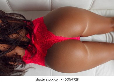 top view of female buttocks in red panties lying on white couch