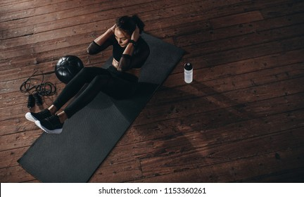 Top view of female doing abdomen workout at the gym. Fit woman on exercise mat with her hands behind head doing stomach exercises.