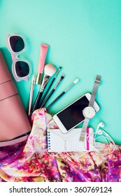 Top view of female fashion accessories for woman. Stylish sunglasses, pink bag, silver watch, lipstick, smart phone, make up brushes,notebook. Overhead of essentials for modern young person.
