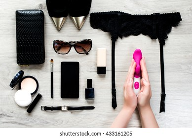 Top view of female fashion accessories for woman. Sex toy in the hands, sunglasses, face powder, make up brush, nail polish, watch, mobile phone, lipstick, gold pointed shoes, purse