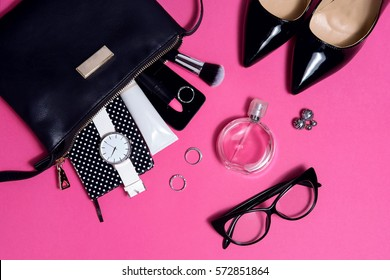 Top view female fashion accessories on pink flat lay . Black glasses, bag , watch , lipstick , perfume and high heel shoes, woman essentials