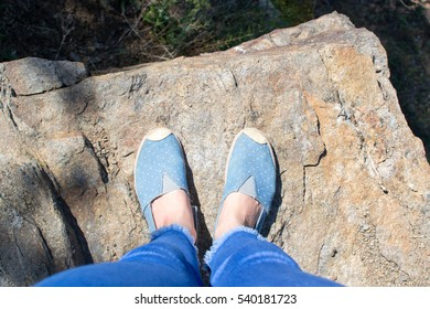 Top view female feet in jeans and sports shoes in public park