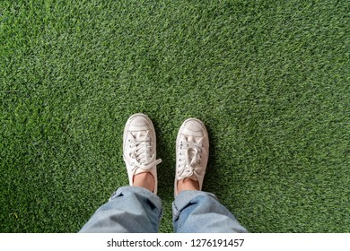 top view of female feet with sneakers standing on  green artificial grass with blank copyspace