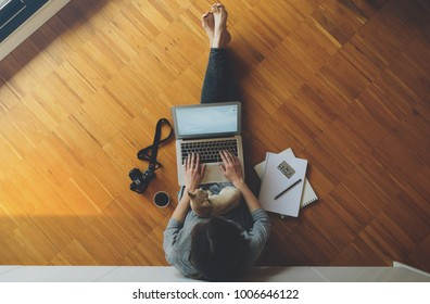 top view of a female freelance photographer working with laptop computer, sitting on a wooden floor with her little dog on her lap. girl looks at photos from vacation. Vintage camera.