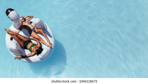 Top view of female friends wearing bikini lying on an inflatable toy in pool. Woman sunbathing on floating pool inflatable toy.