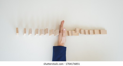 Top view of female hand in elegant blue suit stopping falling dominos from collapsing.