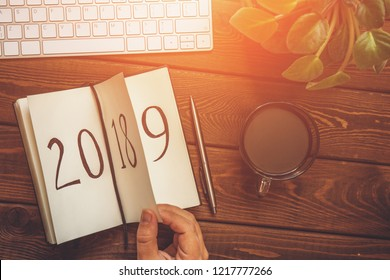 Top view of female hand flips notepad sheet on wooden table. 2018 is turning, 2019 is opening, toned with light effect
