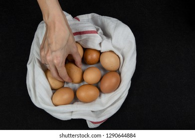 Top view of a female hand picking one fresh egg from a white cloth on a tabletop