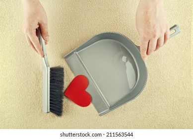 Top View of Female Hand sweeping heart shaped paper from the floor with brush cleaner.