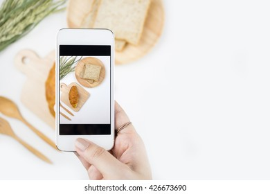 Top view of a female hand taking picture of baked goods with a smartphone, focuses on the hand holding the phone with copy space