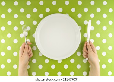 Top view of Female hands at dinner table holding fork and a knife above empty flat white plate, dieting concept.