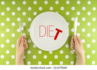 Top View of Female hands at dinner table holding fork and a knife above plate as dieting concept. Word Diet becoming Die referring to health issues that diet mistakes can cause.