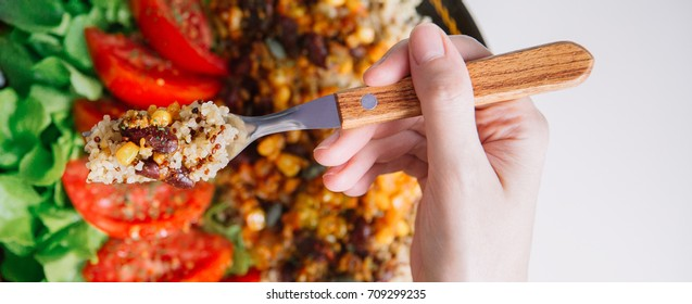 Top view of Female hands at dinner table holding fork above plate with quinoa, red beans, corn, tomato and green salad, close up