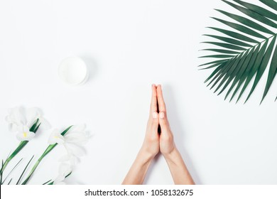 Top view of female hands doing namaste gesture among flowers and palm leaf on white background. Tropical composition with copy space for text.