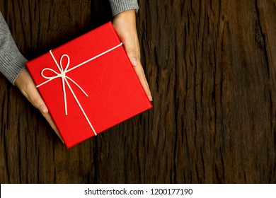 Top view of female hands holding red gift box on wooden background